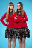 Dos colegialas adolescentes se colocan de lado a lado sobre fondo azul imágenes de archivo libres de regalías