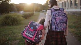 Dos colegialas de las hermanas están caminando a casa de escuela La hermana grande lleva a su hermana más joven a casa de escuela metrajes