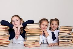 Dos colegialas de las muchachas se sientan con los libros en su escritorio en la lección en la escuela foto de archivo libre de regalías
