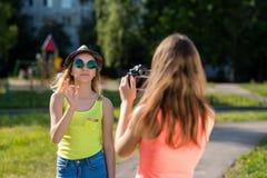 Dos colegialas de un adolescente Vídeo de registro en la videocámara En el verano en la naturaleza de la ciudad Un día soleado br Imagen de archivo