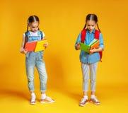 Dos colegialas divertidas de los niños en fondo amarillo fotos de archivo