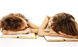Dos colegialas que estudian en el escritorio que está cansado Fotografía de archivo