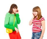 Dos colegialas que llaman por los teléfonos móviles Imágenes de archivo libres de regalías