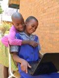 Dos colegialas smilling que usan el ordenador portátil al aire libre fotos de archivo