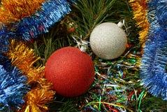 Dos colorearon bolas del ` s del Año Nuevo entre los ornamentos y las agujas brillantes Fotos de archivo