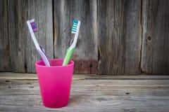 Dos colorearon los cepillos de dientes que se sentaban en una taza plástica rosada Foto de archivo