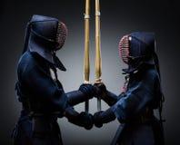 Dos combatientes del kendo con shinai enfrente de uno a Fotos de archivo