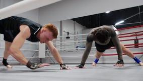 Dos combatientes están entrenando en ringside hacen ejercicios en tablón en club de la lucha almacen de video