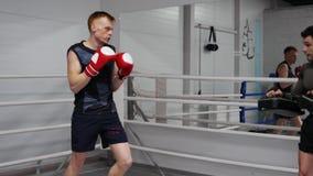 Dos combatientes profesionales jovenes están entrenando a retrocesos en ringside en club de la caja de la lucha metrajes
