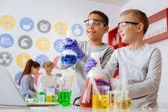 Dos compañeros de clase optimistas que son sorprendidos con la reacción química Fotografía de archivo