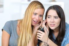 Dos compañeros de cuarto que escuchan la misma conversación móvil en casa fotografía de archivo