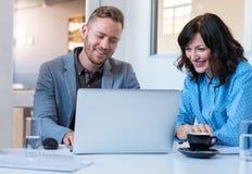 Dos compañeros de trabajo jovenes sonrientes que usan un ordenador portátil en una oficina Foto de archivo