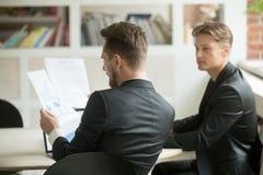 Dos compañeros de trabajo de los hombres de negocios que analizan informe financiero del stats Imagen de archivo
