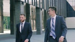 Dos compañeros de trabajo masculinos elegantes que van a trabajar en el día almacen de video
