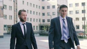 Dos compañeros de trabajo masculinos elegantes que van a trabajar por la mañana almacen de video