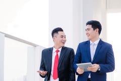Dos compañeros de trabajo masculinos vietnamitas que hablan y que sonríen foto de archivo libre de regalías