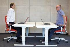 Dos compañeros de trabajo que ejercitan en las butacas en los puestos de trabajo en oficina Imagenes de archivo