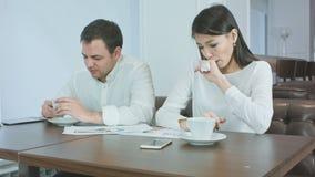 Dos compañeros de trabajo que no sienten té caliente bien y de consumición durante almuerzo en un café almacen de video