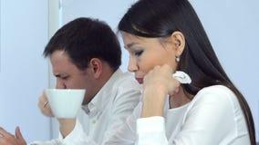 Dos compañeros de trabajo que sienten té caliente mal y de consumición durante almuerzo en un café almacen de video