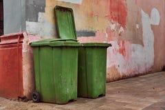 Dos compartimientos de basura verdes cerca de la pared multicolora vieja Fotos de archivo libres de regalías