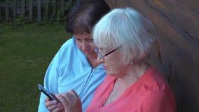 Dos concentraron a las mujeres mayores que miraban en smartphone metrajes