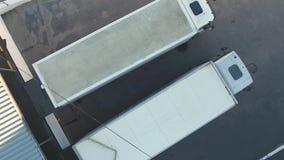Dos conductores de camión se sientan en la rueda y salen de la base del cargamento metrajes