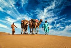 Dos conductores del camello de los cameleers con los camellos en dunas Fotografía de archivo libre de regalías