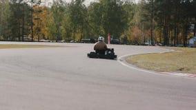 Dos conductores en una pista del ir-kart pasan por la cámara Va-Kart la raza almacen de video