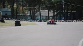 Dos conductores en una pista del ir-kart se trasladan a la cámara y la pasan cerca Va-Kart la raza almacen de metraje de vídeo