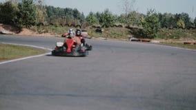 Dos conductores en una pista del ir-kart se trasladan a la cámara y la pasan cerca Va-Kart la raza almacen de video