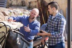 Dos conductores que trabajan con el tractor Imágenes de archivo libres de regalías