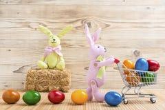Dos conejitos de pascua con un carro de la compra y muchos huevos de Pascua coloridos Foto de archivo libre de regalías