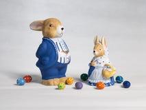 Dos conejitos de pascua hombre y mujer con los huevos y la cesta Imágenes de archivo libres de regalías