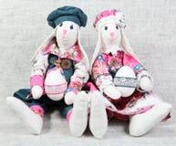Dos conejitos de pascua que sostienen los huevos Fotos de archivo libres de regalías