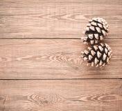 Dos conos del pino en una tabla de madera Misterio de la Navidad imagen de archivo