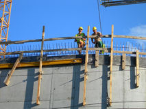 Dos constructores. Trabajadores encima de un edificio construido Imagenes de archivo
