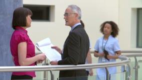 Dos consultores que se encuentran en la recepción del hospital almacen de metraje de vídeo