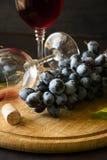 Dos copas con el vino rojo y las uvas Imagen de archivo