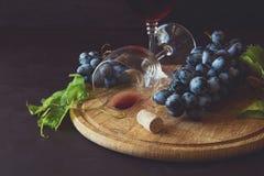 Dos copas con el vino rojo y las uvas Foto de archivo