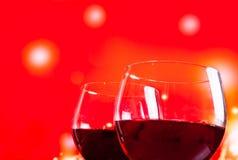 Dos copas de vino rojas cerca de la botella contra fondo de las luces rojas Foto de archivo libre de regalías