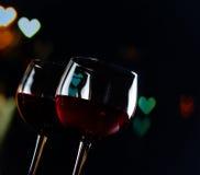 Dos copas de vino rojas en bokeh de la decoración de los corazones encienden el fondo Foto de archivo