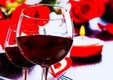 Dos copas de vino rojas en fondo de la decoración de los corazones y de las rosas de la falta de definición Foto de archivo