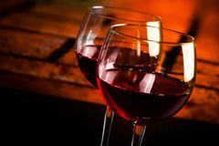 Dos copas de vino rojas en la tabla de madera con el fondo caliente de la atmósfera Fotos de archivo libres de regalías