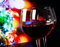 Dos copas de vino rojas en la tabla de madera contra el árbol de navidad encienden el fondo Fotos de archivo