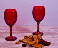 Dos copas de vino rojas sobre el tablero de madera imágenes de archivo libres de regalías