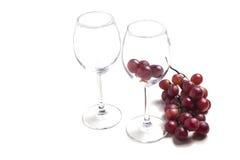 Dos copas de vino vacías con el manojo de uvas Imágenes de archivo libres de regalías