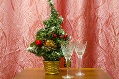 Dos copas de vino y un árbol de navidad artificial Foto de archivo
