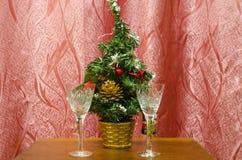 Dos copas de vino y un árbol de navidad artificial Imágenes de archivo libres de regalías