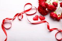 Dos corazones, cinta roja y rosas hermosas Fotografía de archivo