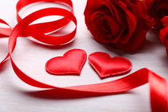 Dos corazones, cinta y rosas rojas en la tabla Fotos de archivo libres de regalías